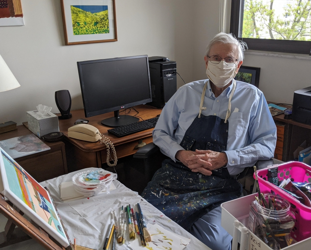 Rev. F. Reid Isaac sits in his study turned art studio.
