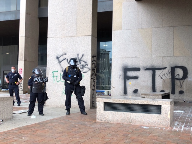 Cleveland police officers stand in front of graffiti from Saturday's protest.