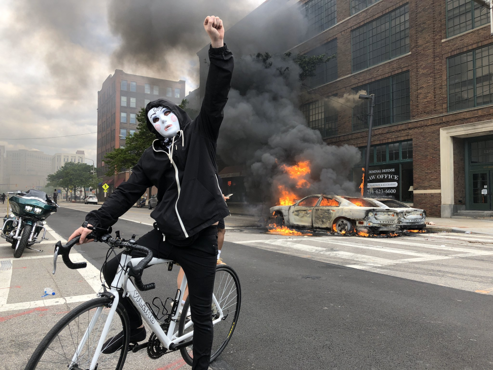Masked person in front of burning vehicles in Cleveland