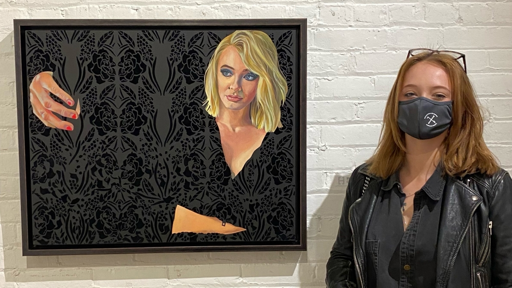 Ruby Jackson poses for a photo in front of a painting of herself.