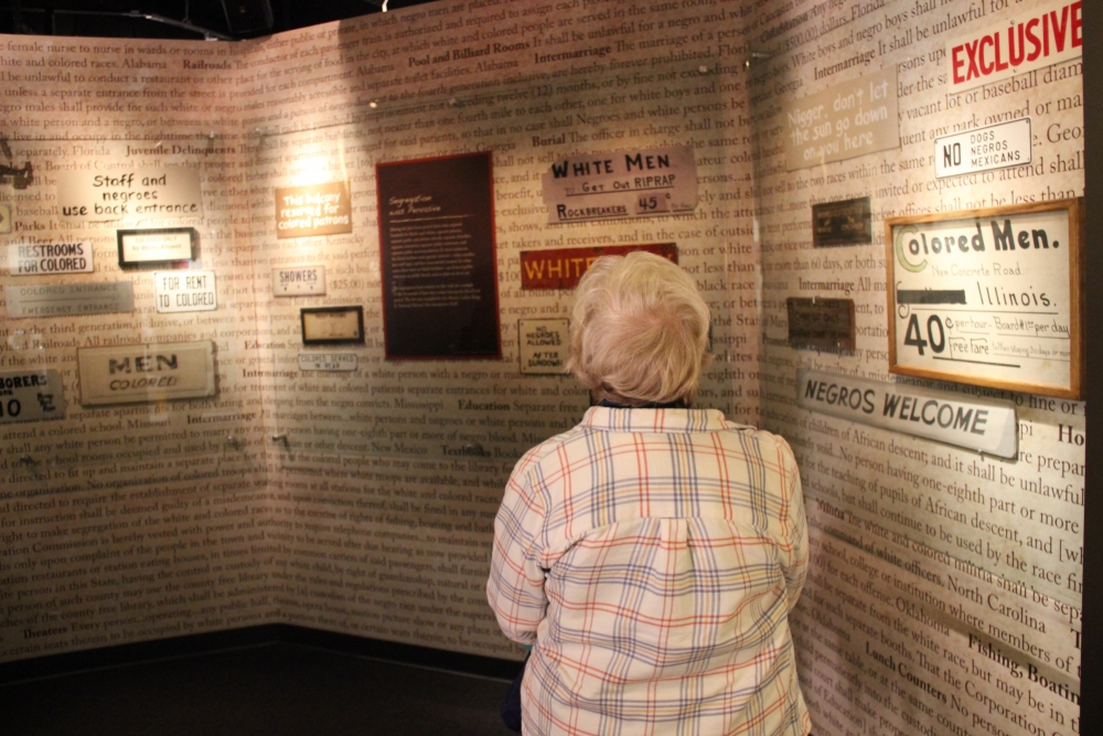 A museum visitor looks at segregation signs on view at the Jim Crow Museum of Racist Memorabilia. [Jim Crow Museum]