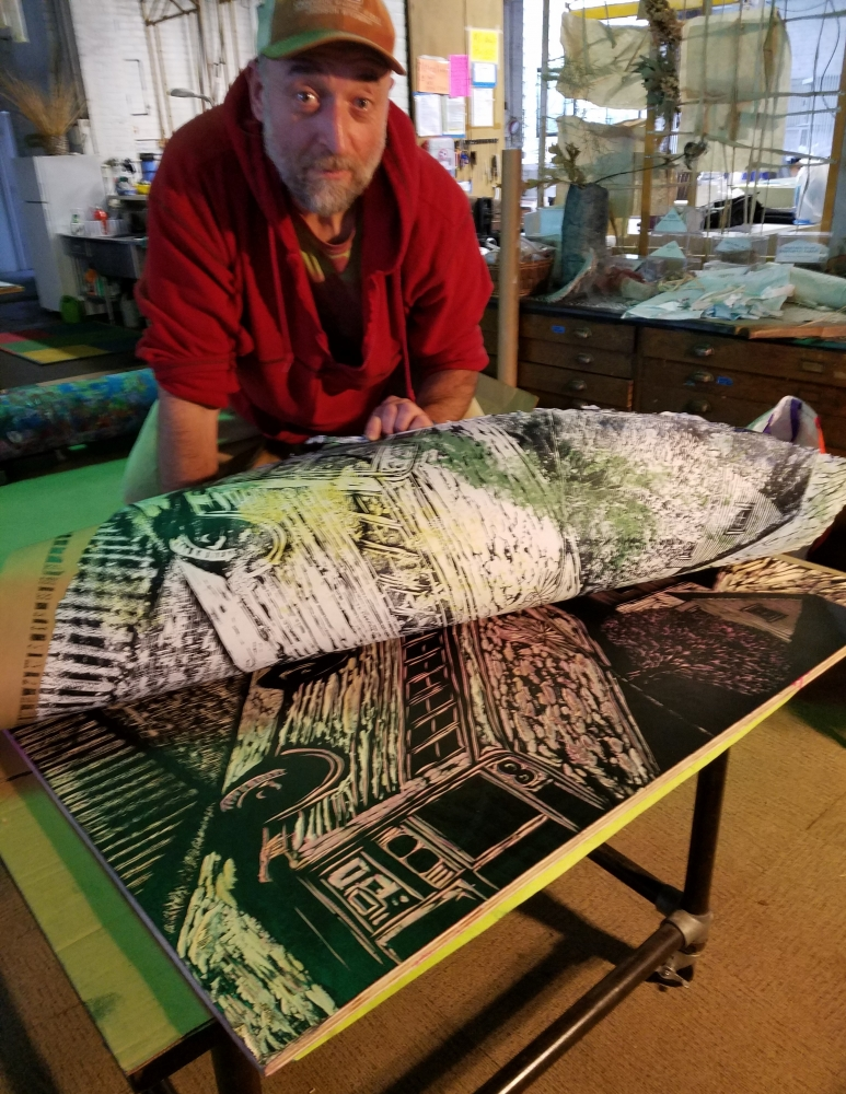 Claudio Orso removing print from the carved woodblock
