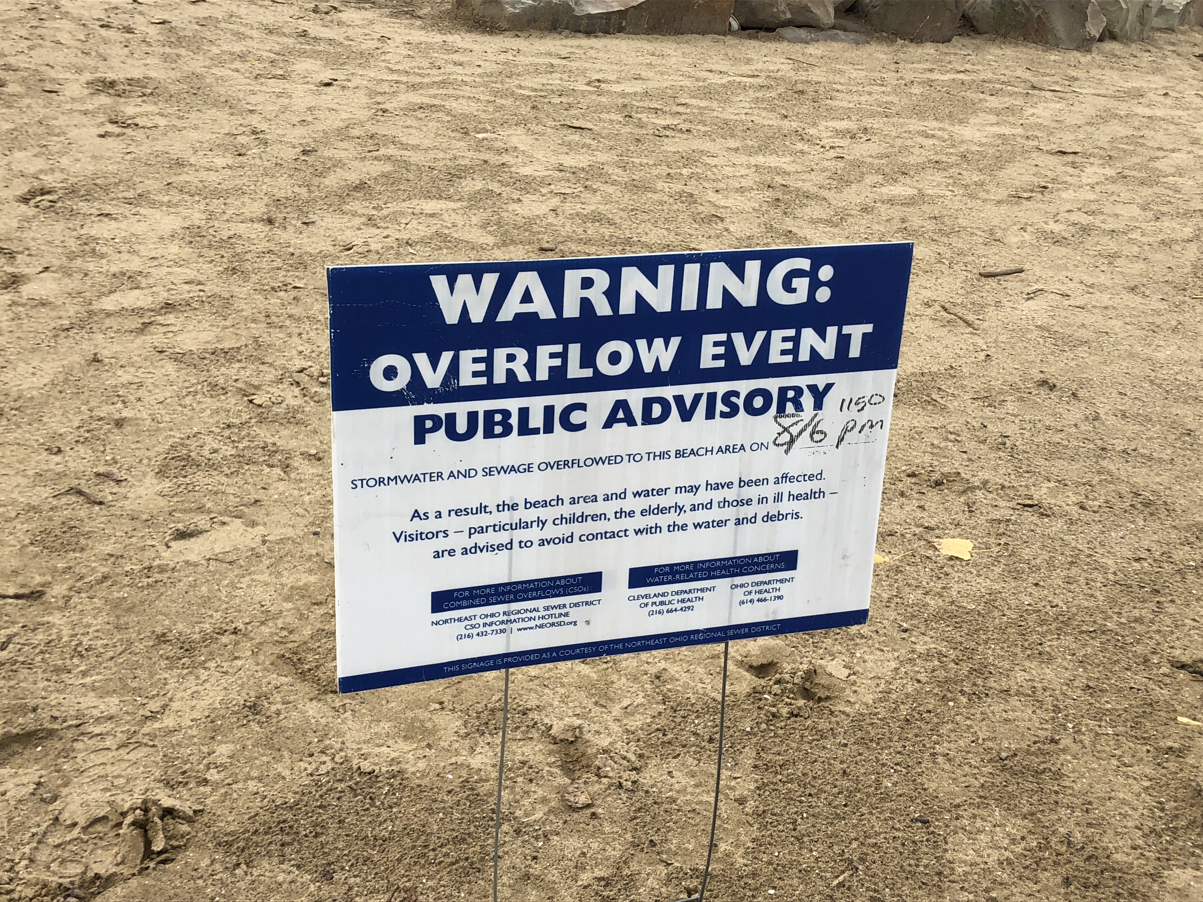Signs warning of sewer overflow entering Lake Erie at Edgewater Beach in Cleveland.