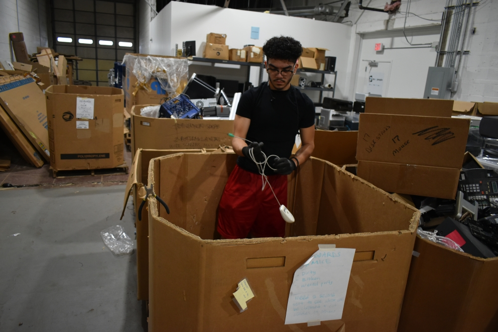 Jovanti Ramirez, a CMSD student who has a summer internship with PCs for People, works to sort mice and other devices out of a bin in PCs for People's warehouse in Cleveland. [Conor Morris / Northeast Ohio Solutions Journalism Collaborative]