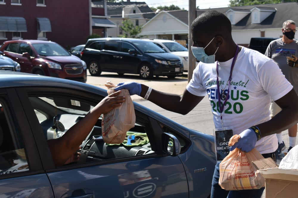 Billy L. Sharp, guild president of the Urban League Guild of Greater Cleveland, hands out food and census information during a July food bank event at Mt. Gillion Baptist Church in central Cleveland.