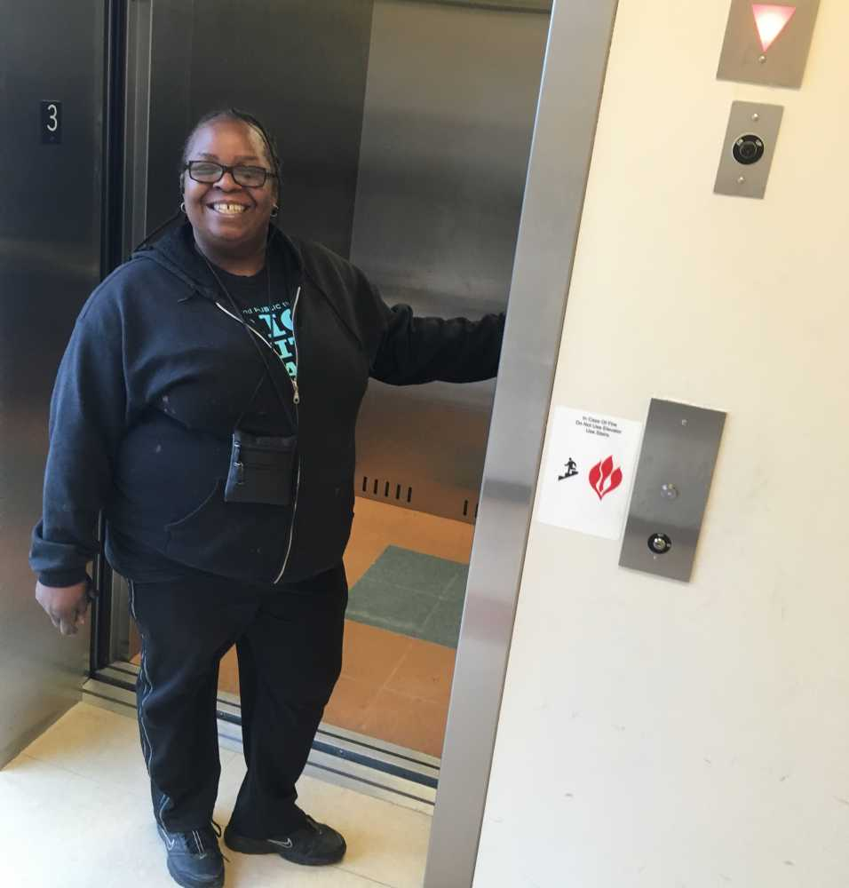 Woodhill public housing resident Jeanette Marbley holds the door open on an elevator.