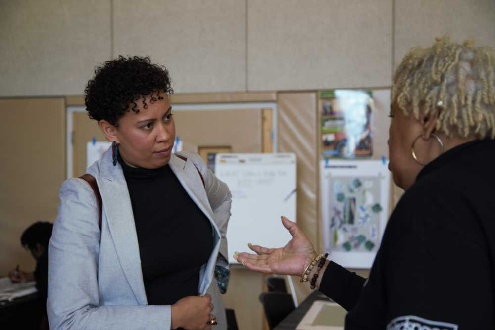 Cuyahoga Metropolitan Housing Authority's Indigo Bishop talks with a Woodhill resident.