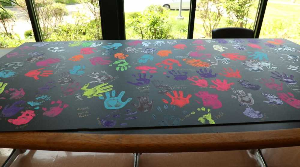 The new mural at Woodhill Homes shows colorful handprints.