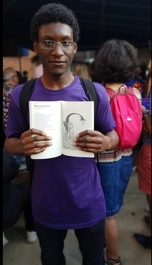 Caillou Allen stands with a copy of his self-published book.