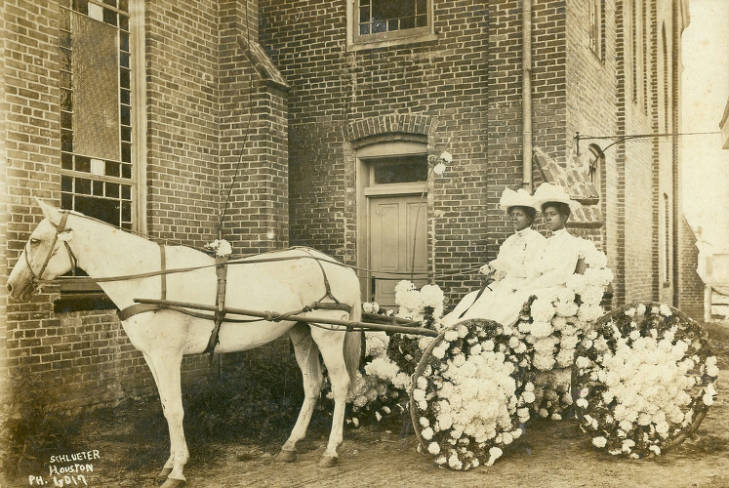 Two women sit in a buggy for an early Juneteenth celebration in Houston in 1908.