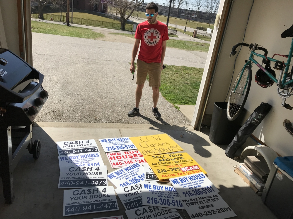 Brandon Kirsch stands over the signs he stores in the garage of his Cleveland townhouse.