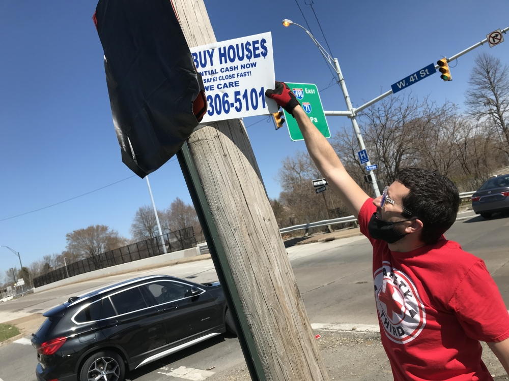 Brandon Kirsch tears down a 'We Buy Houses' sign in Cleveland.