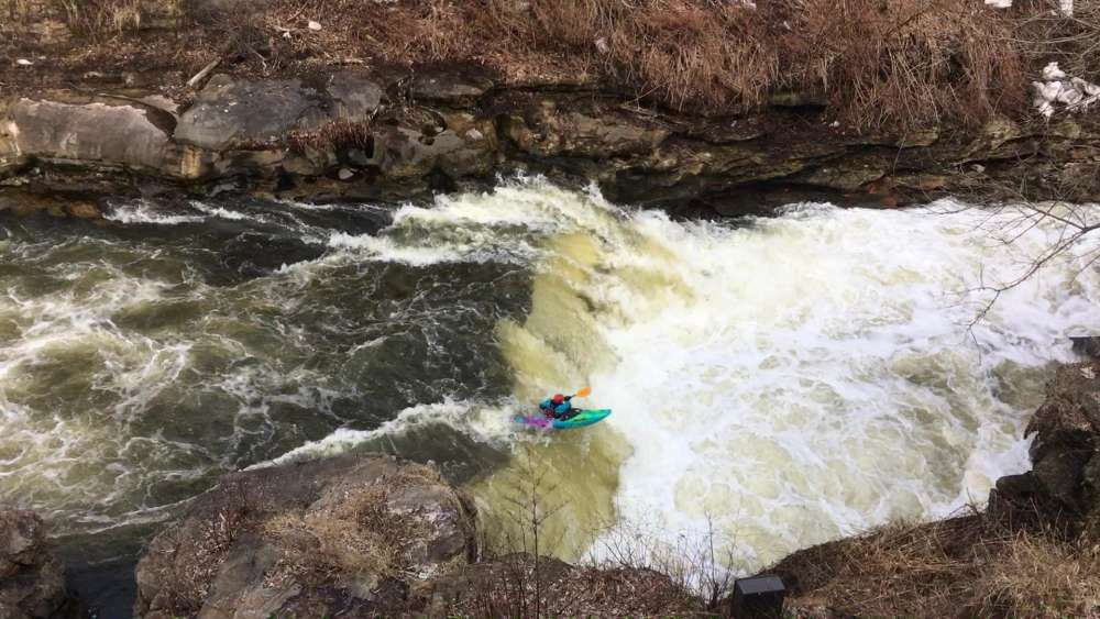 A kayaker going over a fall.