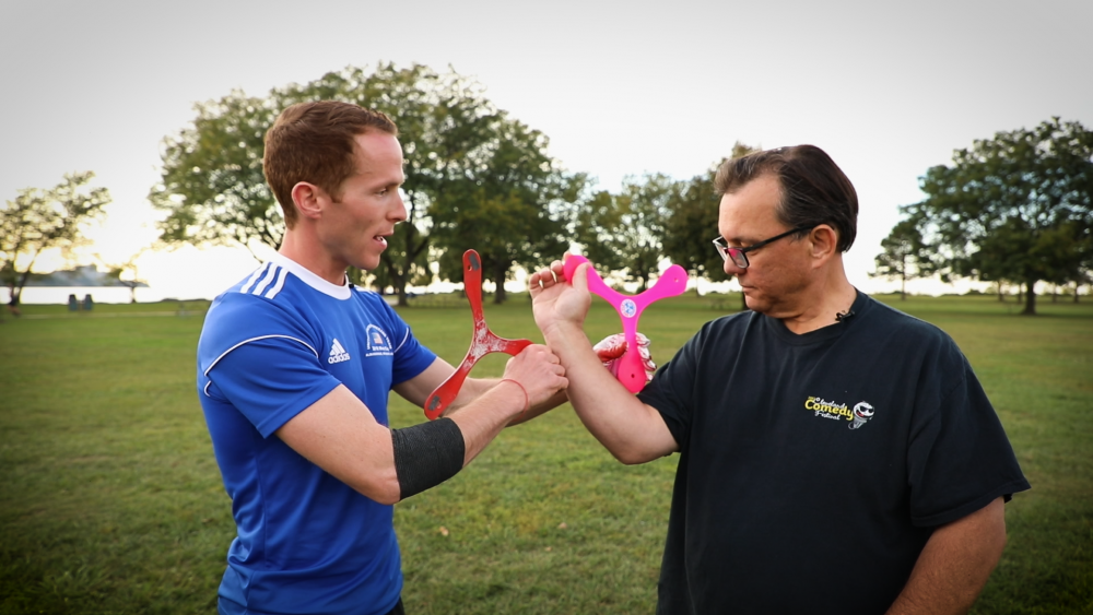 Logan Broadbent teaches ideastream's Mike McIntyre how to hold and throw a boomerang.